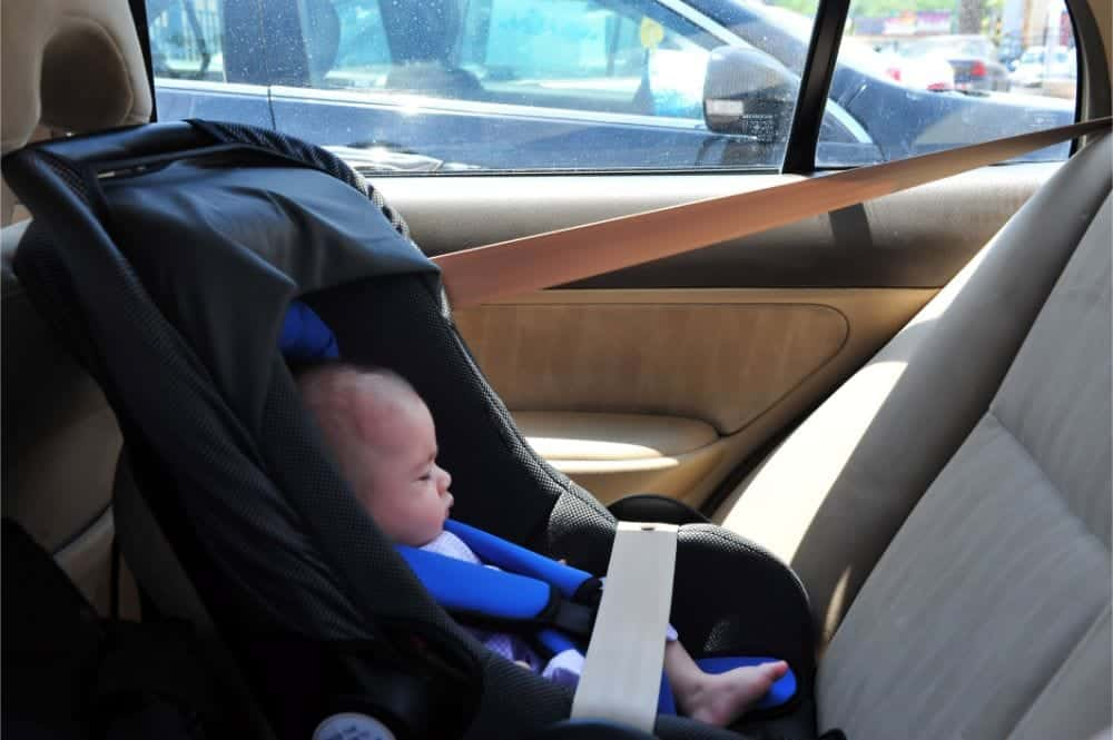 Sleeping infant in a rear facing narrow car seat