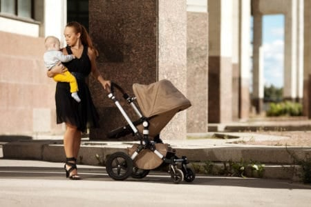 Fashionable modern mother pushing a luxury stroller