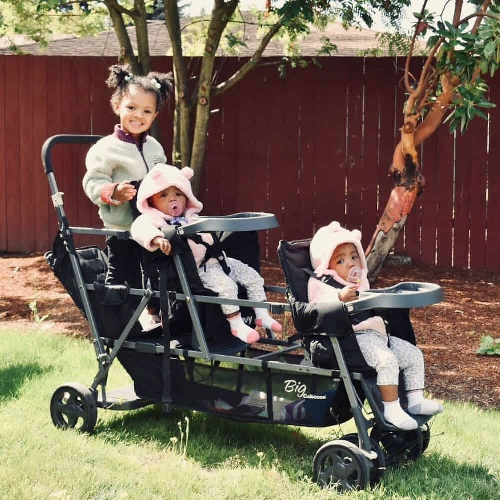 Three children sitting in a triple stroller