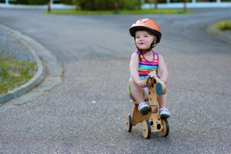 Toddler riding a bike wearing a helmet