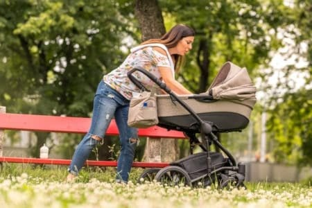 Mother checking her baby in a stroller