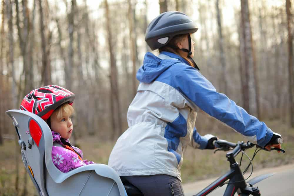 Mother riding a bicycle with daughter in a bike seat