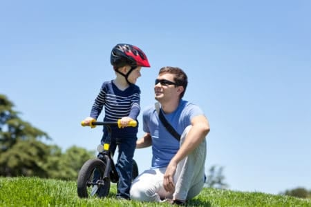 Father teaching son how to ride a balance bike