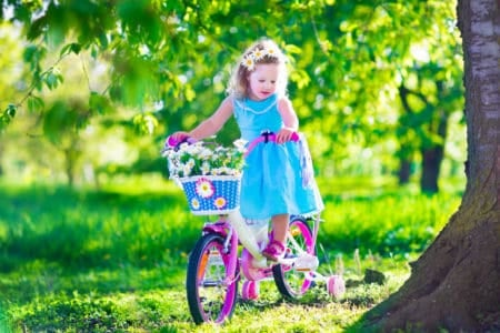 Little girl riding a pink bike