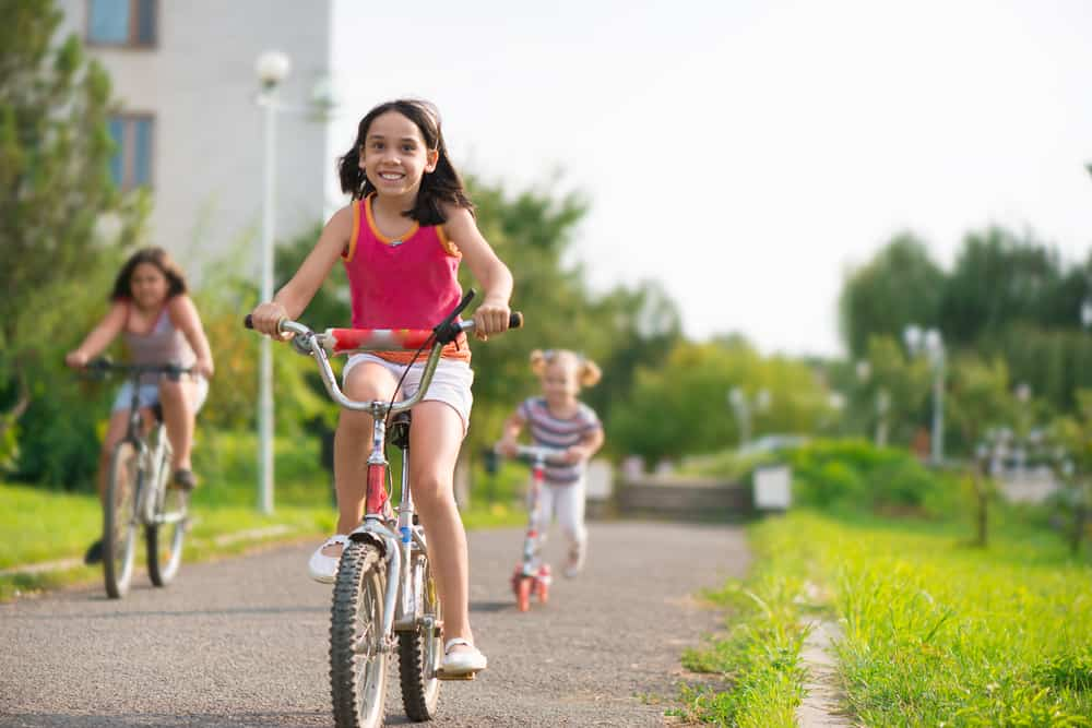 Three children riding bicycles and a scooter