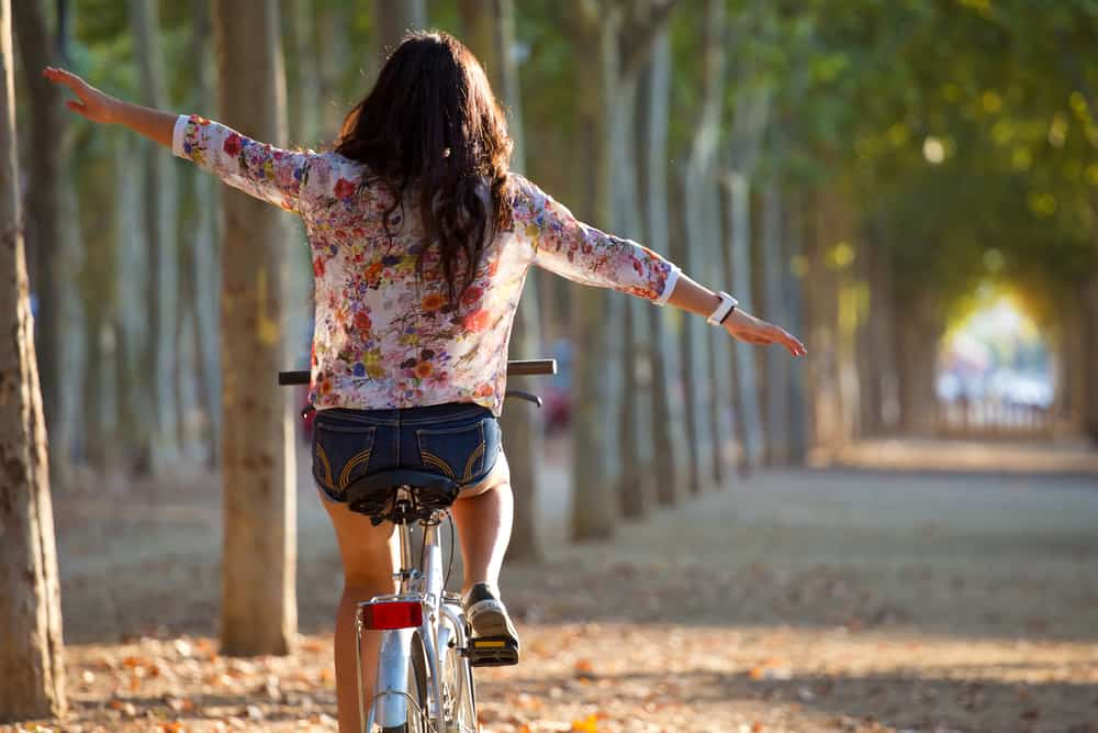 Young girl riding a bike with outstretched arms