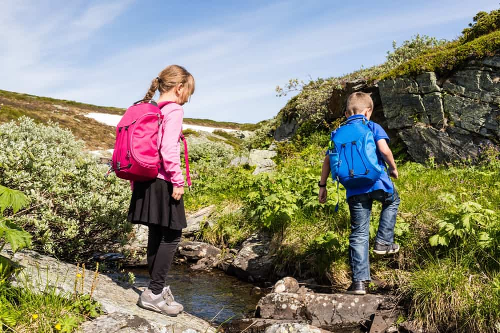 Two kids hiking with hydration backpacks