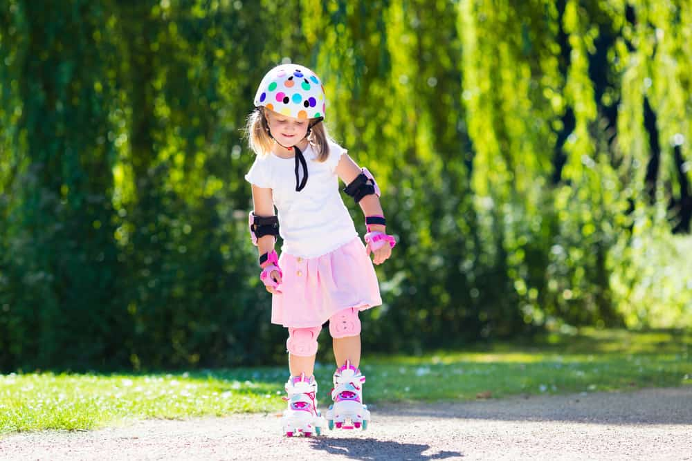 Little girl wearing knee and elbow pads