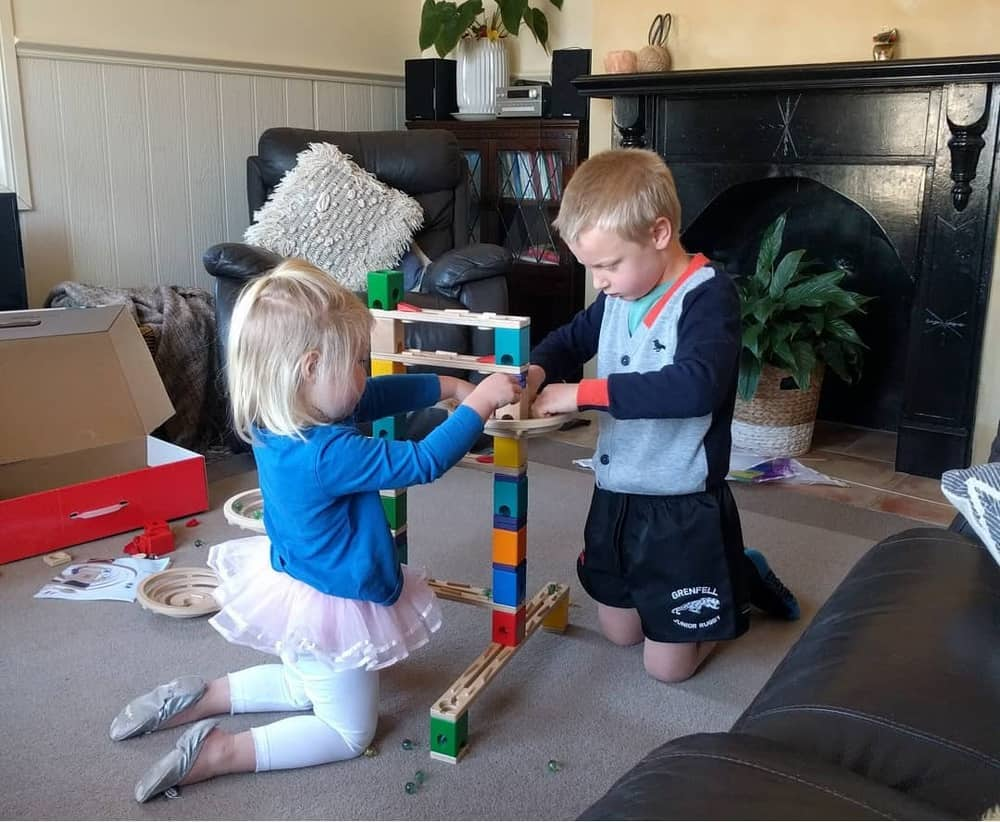 Little boy and girl playing with a marble run toy