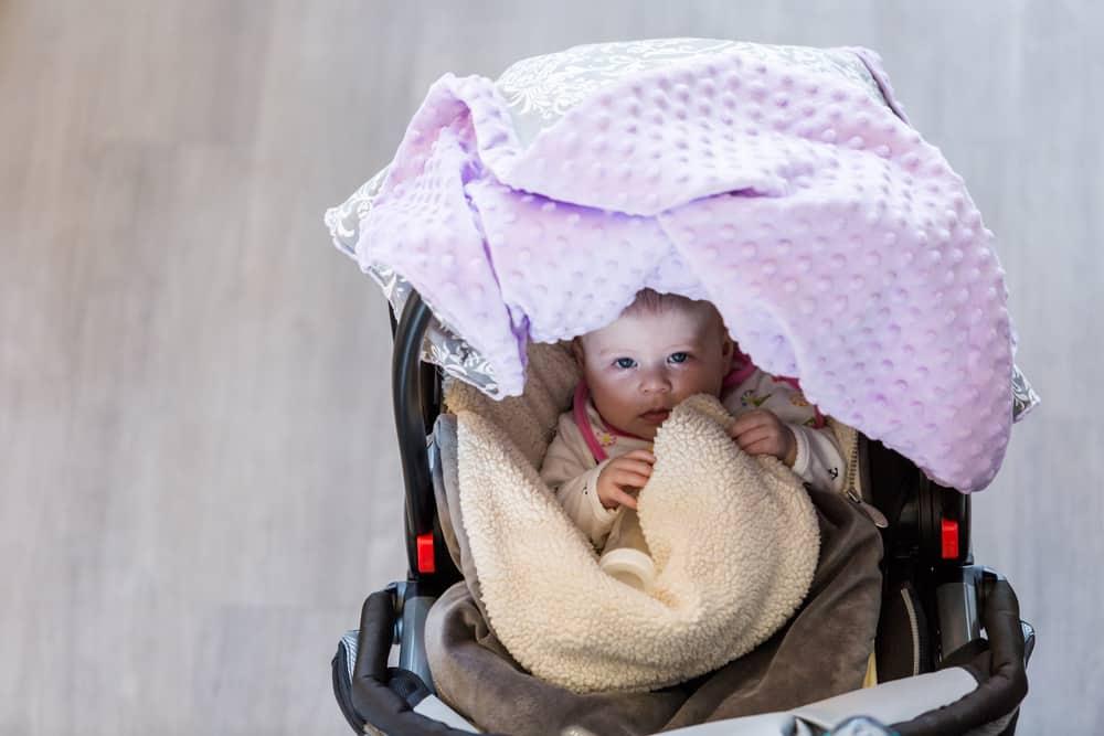 Baby in a stroller wearing a blanket