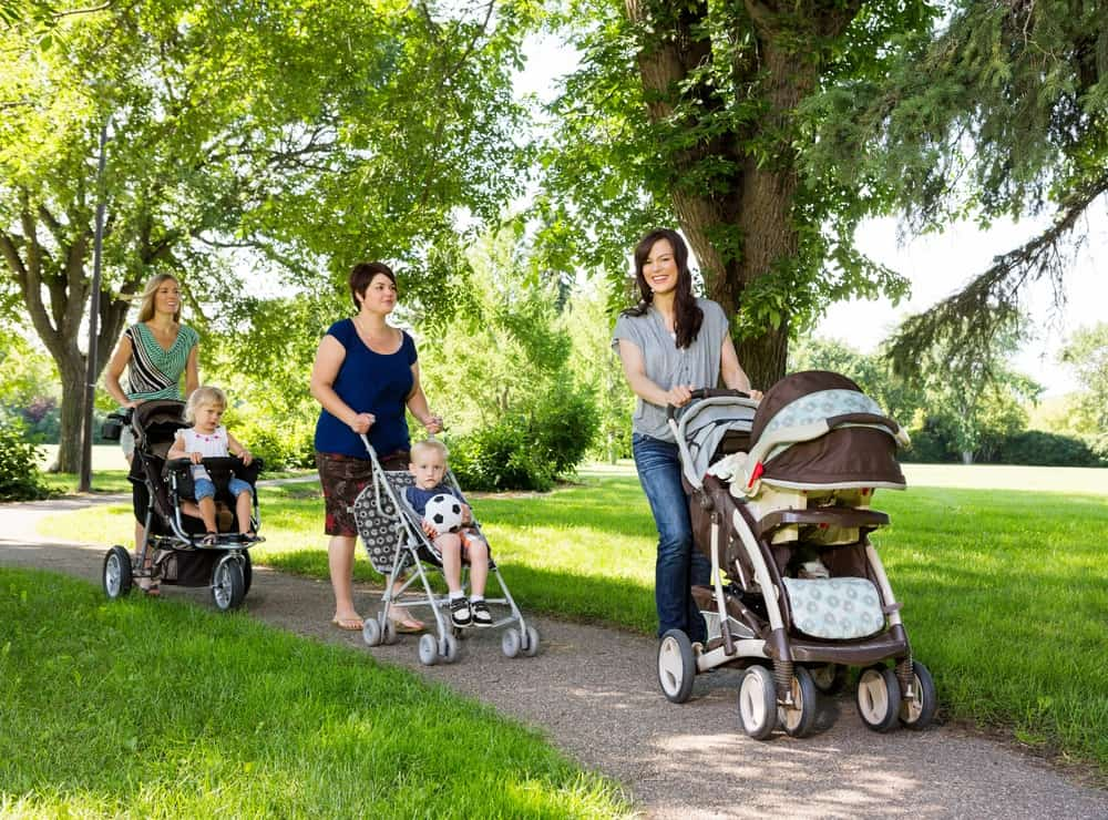 Mothers walking their babies in different kinds of strollers