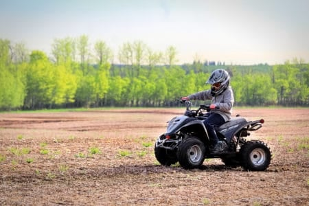 Young boy driving an ATV on a field