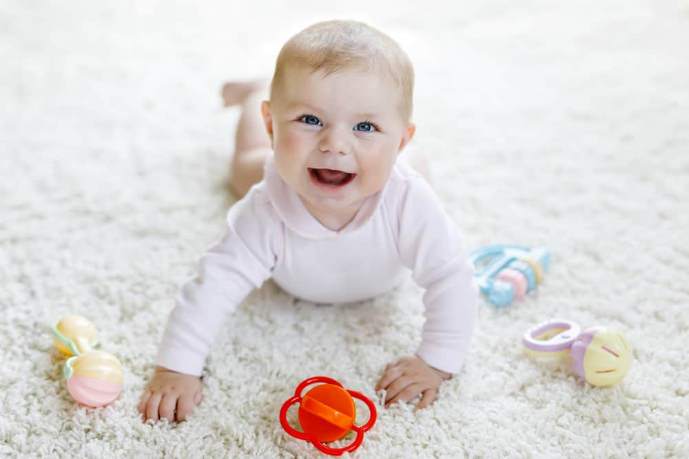 Baby happily playing with tummy time toys