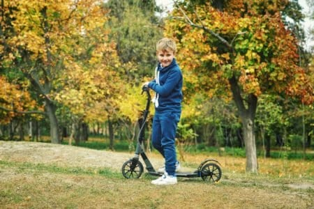 Young boy driving an electric scooter at the park