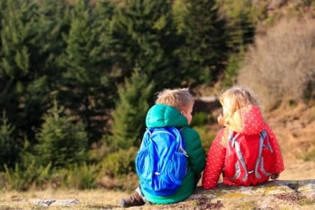 Toddlers wearing backpacks hiking in the mountains