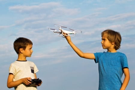 Kids playing with a drone outdoors.