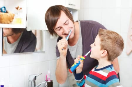 Father teaching son to use an electric toothbrush