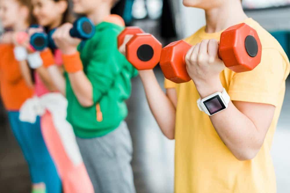 Kids with fitness tracker lifting weights