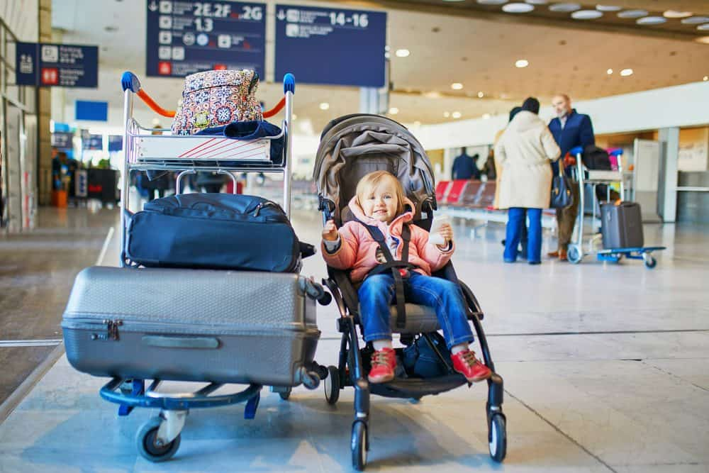 Toddler in a travel stroller at an airport