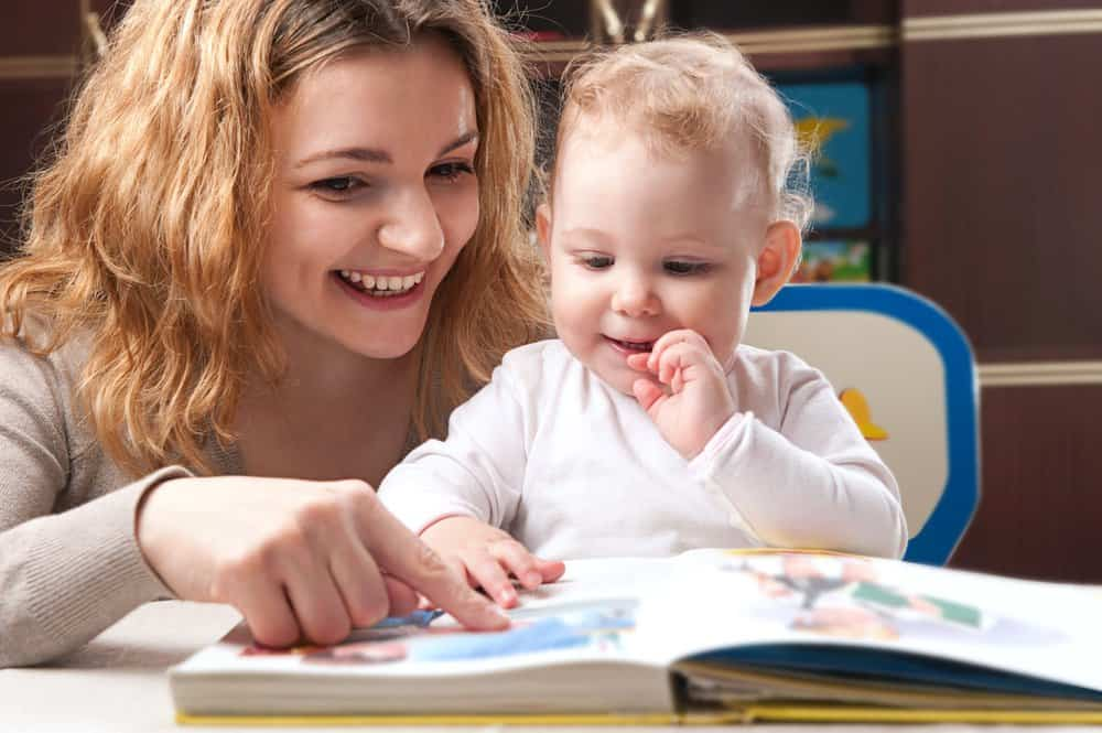 Mother reading an interactive children's book with baby daughter