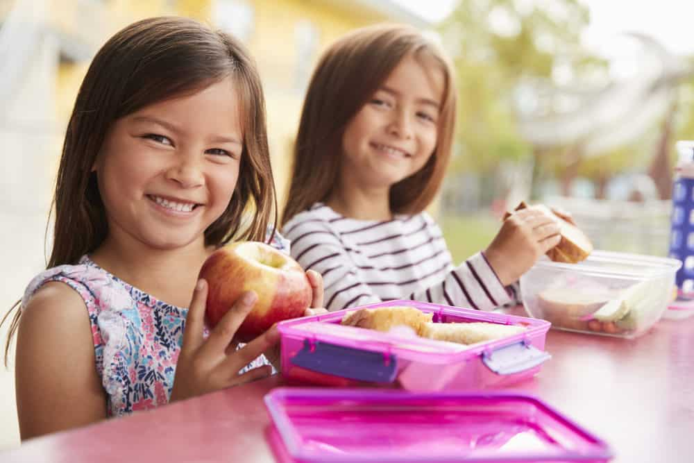 Two young schoolgirls eating food from their lunch boxes
