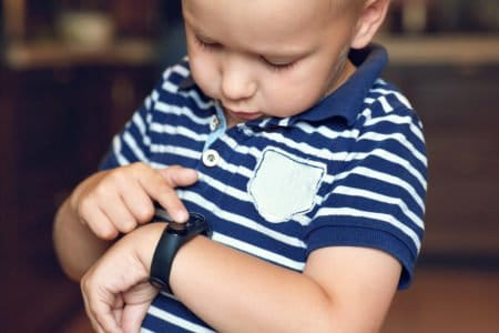 Little boy playing with his fitbit