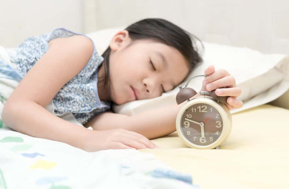 Little girl sleeping while holding an alarm clock