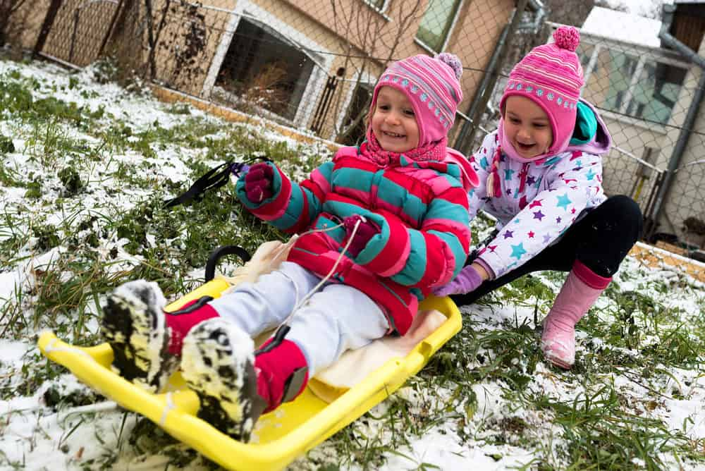 Little kids playing outside with snow sleds