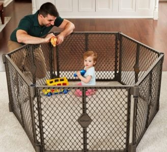 Toddler playing inside a baby fence