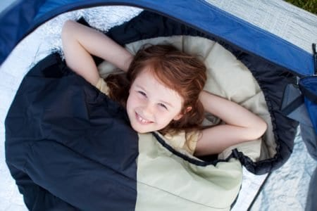 Smiling little girl lying in a sleeping bag
