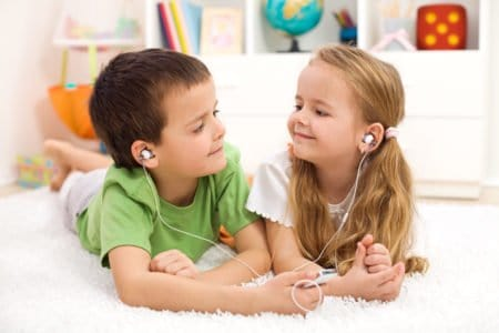 Kids sharing earphones listening from an mp3 player