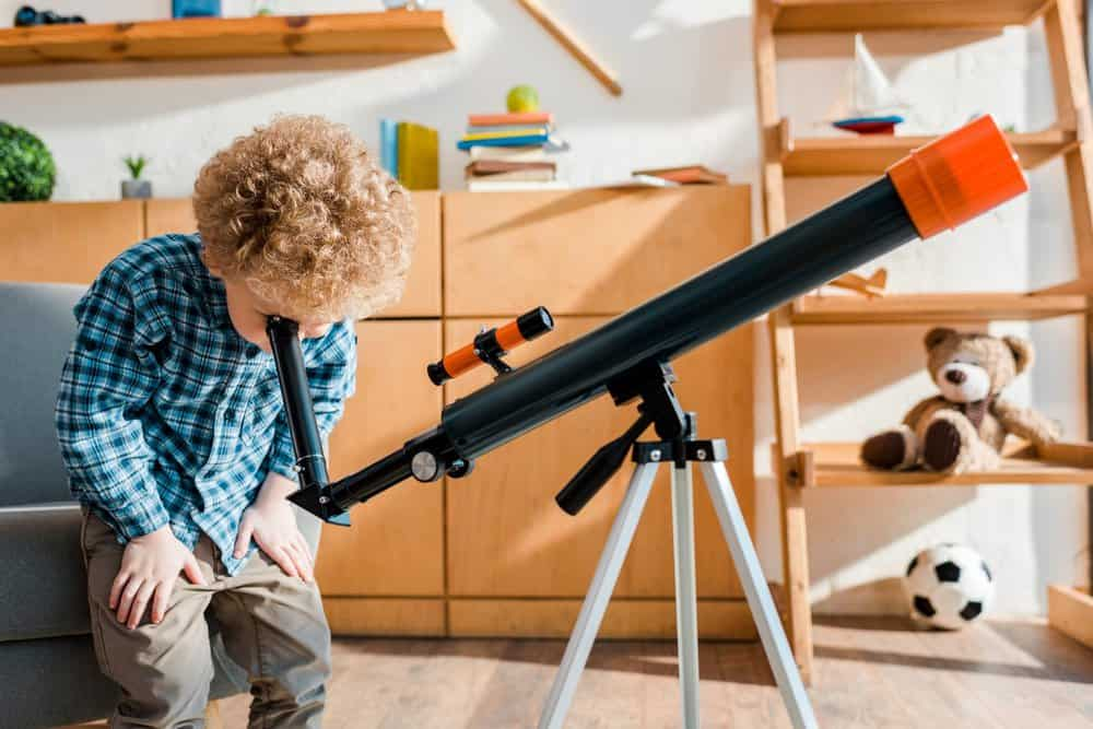 Little boy viewing from a telescope