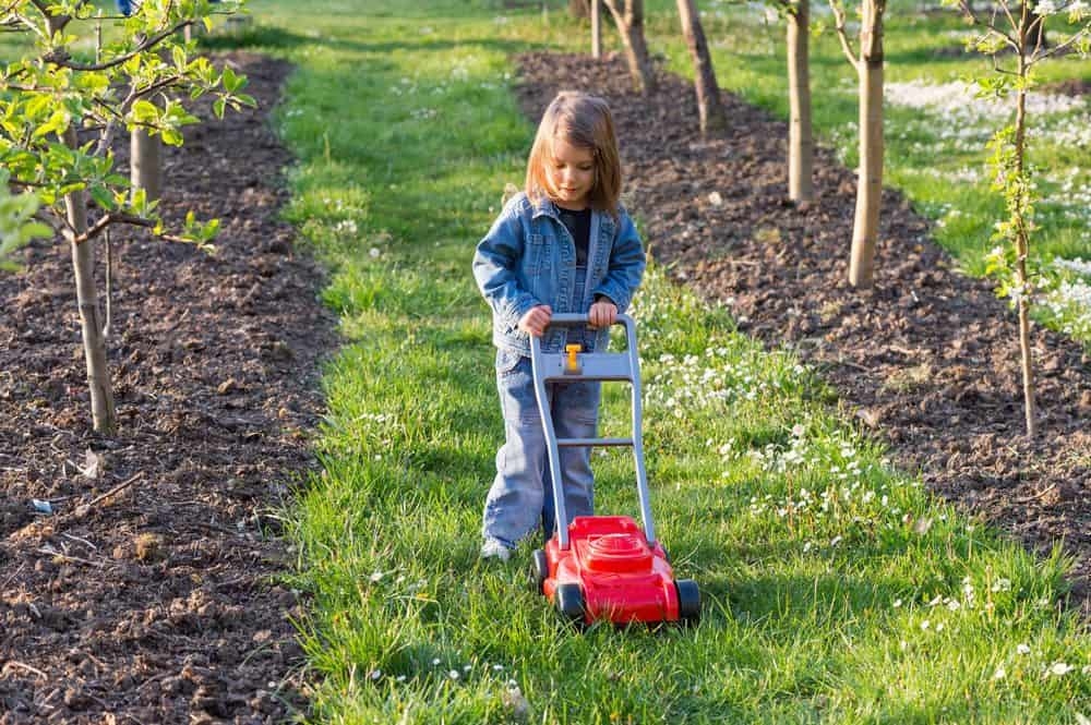 Little girl playing with a toy lawn mower outdoors
