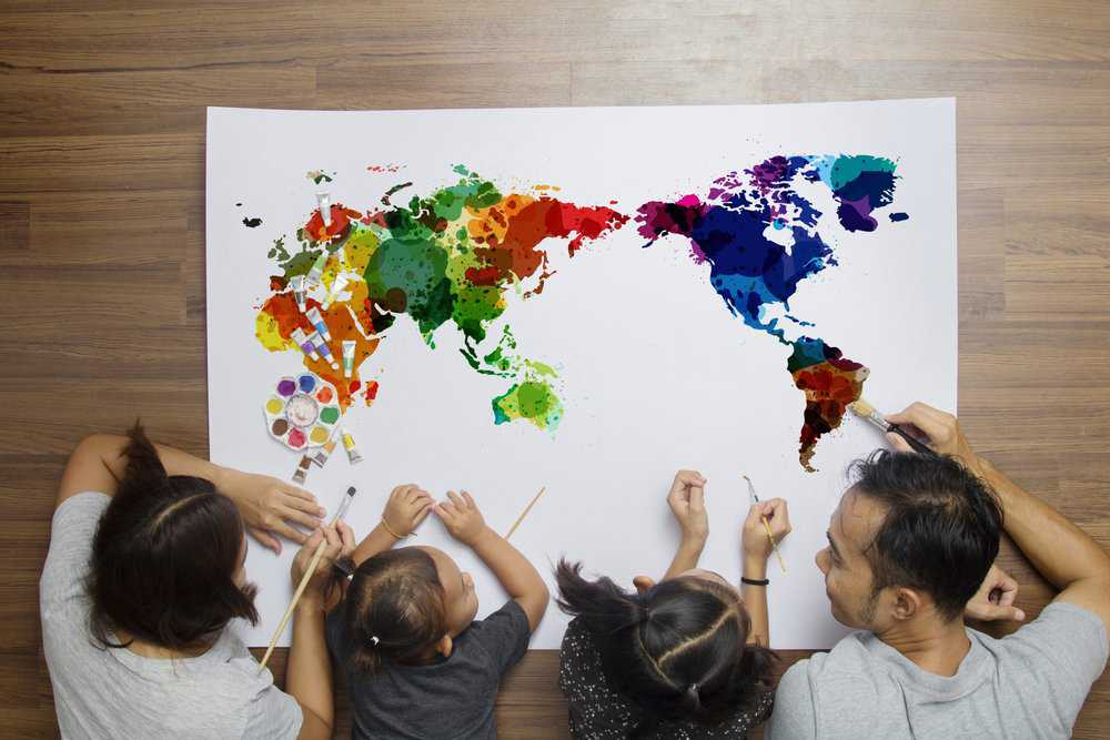 Happy happy family lying on floor with painting a world map