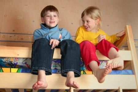 Two siblings chatting on the top bunk bed