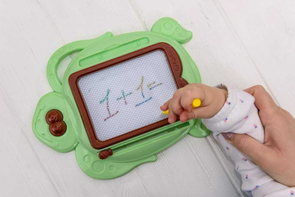 Toddler doodling on a magnetic drawing board