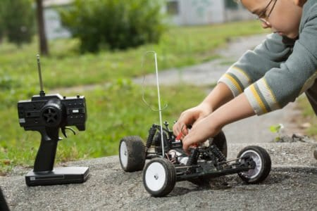 Young boy playing with a remote controlled car