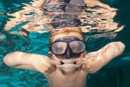 A young goofy boy swimming with goggles