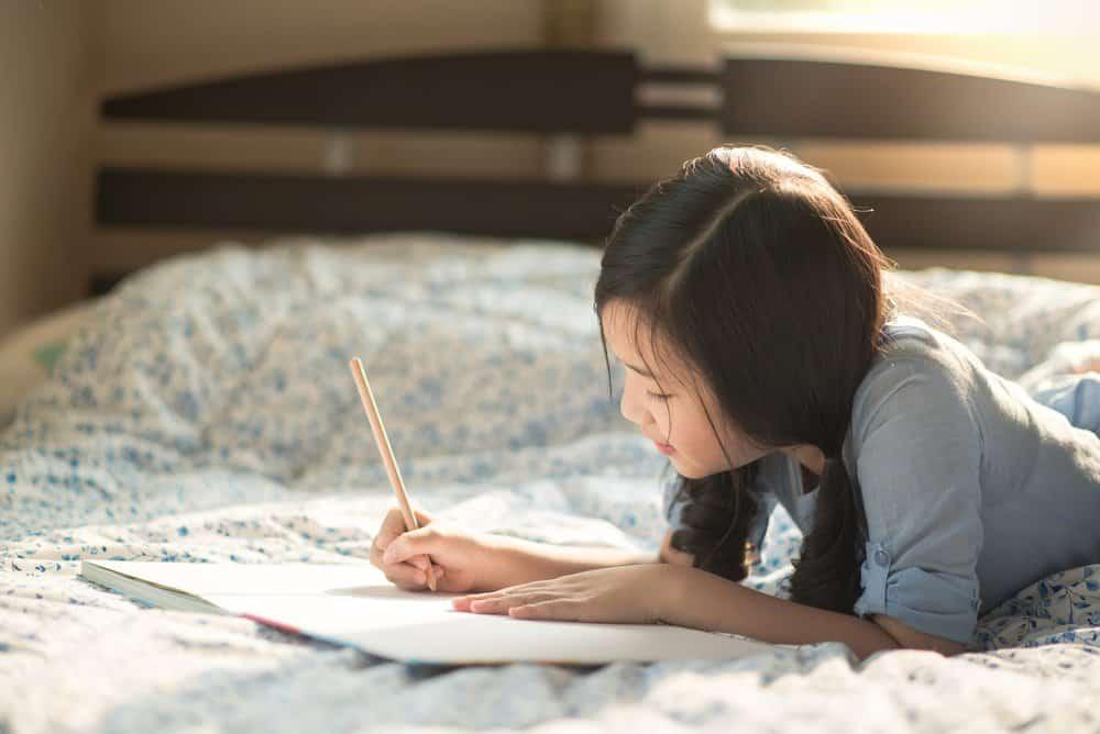 Beautiful young girl writing in her journal