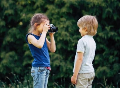 Older sister takes a photo of her brother