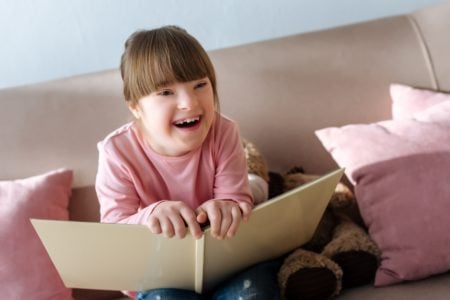 Beautiful little girl laughing while reading a funny poem