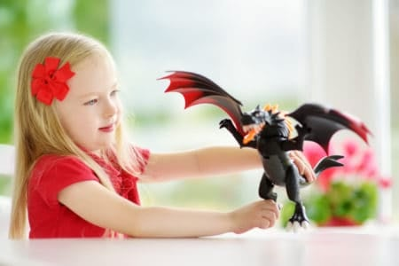 Cute little girl playing with toy dragon at home