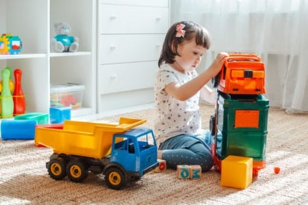 Little girl playing with toy garbage trucks