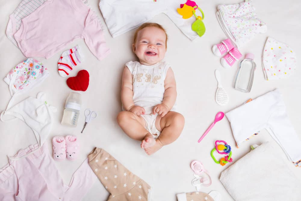 Cute baby surrounded by baby stuff