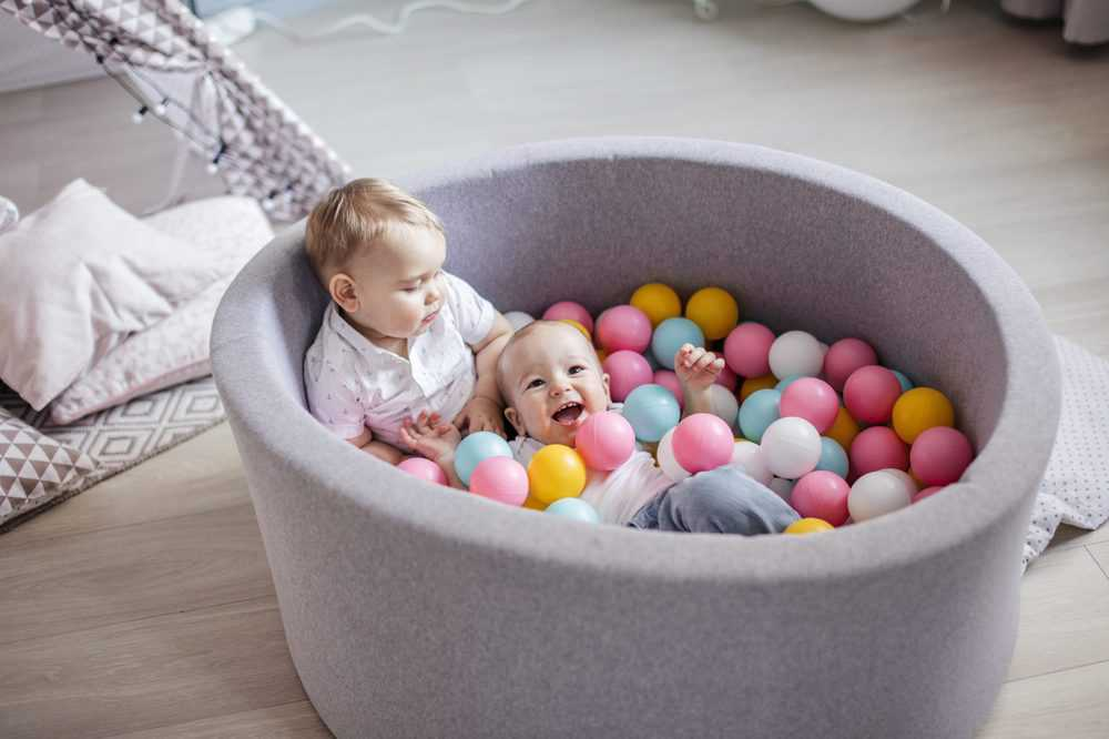 Little cute happy kids play with balls in ball pit
