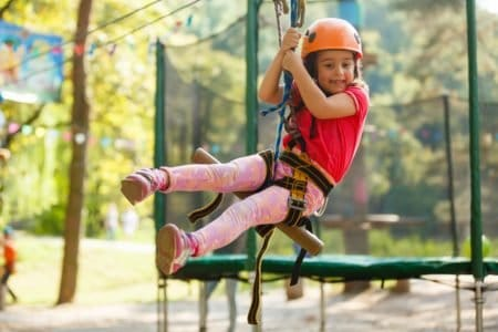 Little girl hanging on zipline
