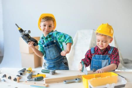 Cute kids playing with construction tool sets