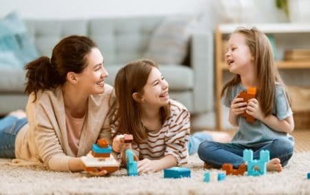 Happy mom and daughters play with lego sets