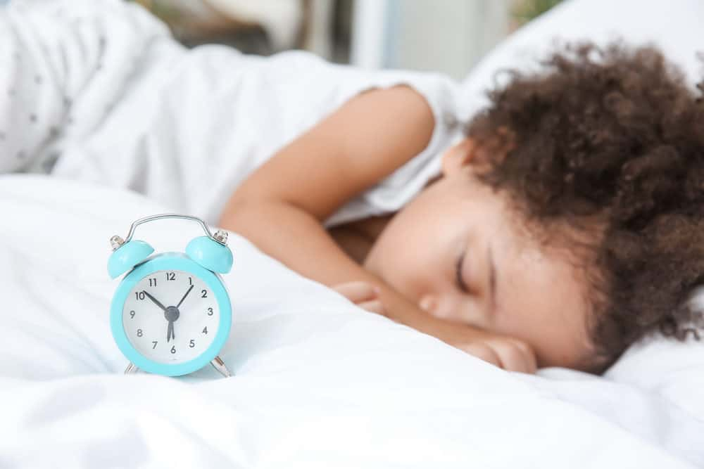 Little toddler sleeping with an alarm clock