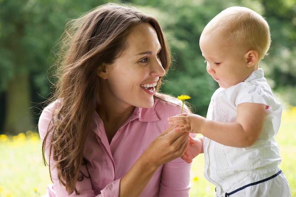 Happy mother giving flower to baby